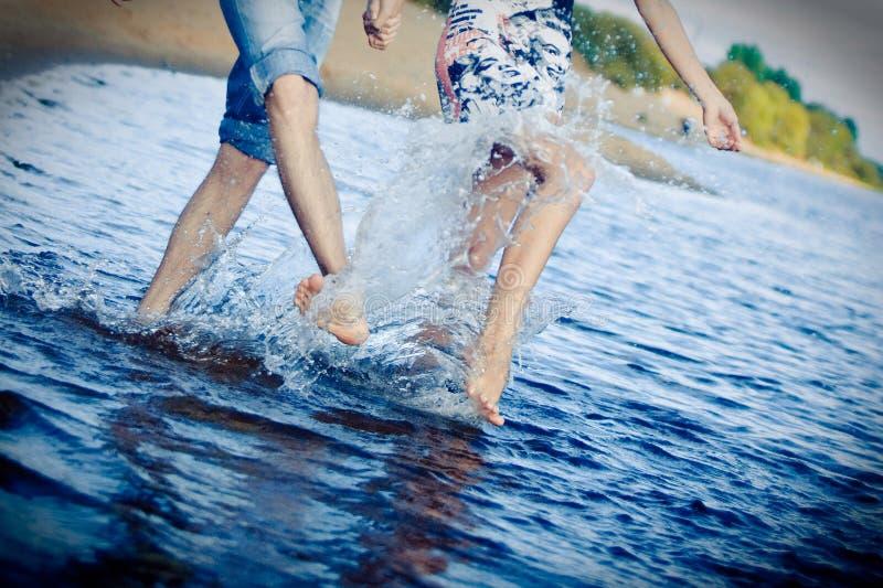Pares que salpican en la playa fotografía de archivo