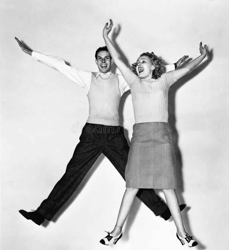 Pares que saltan con sus brazos extendidos (todas las personas representadas no son vivas más largo y ningún estado existe Garant fotografía de archivo