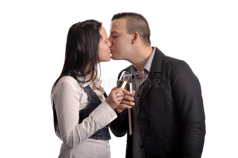 Pares que se besan de los jóvenes con el vidrio de champán fotografía de archivo libre de regalías