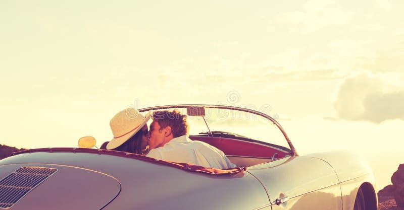 Pares que se besan en coche de deportes clásico del vintage imágenes de archivo libres de regalías