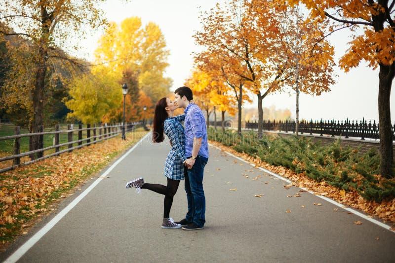 Pares que se besan en parque del otoño fotos de archivo
