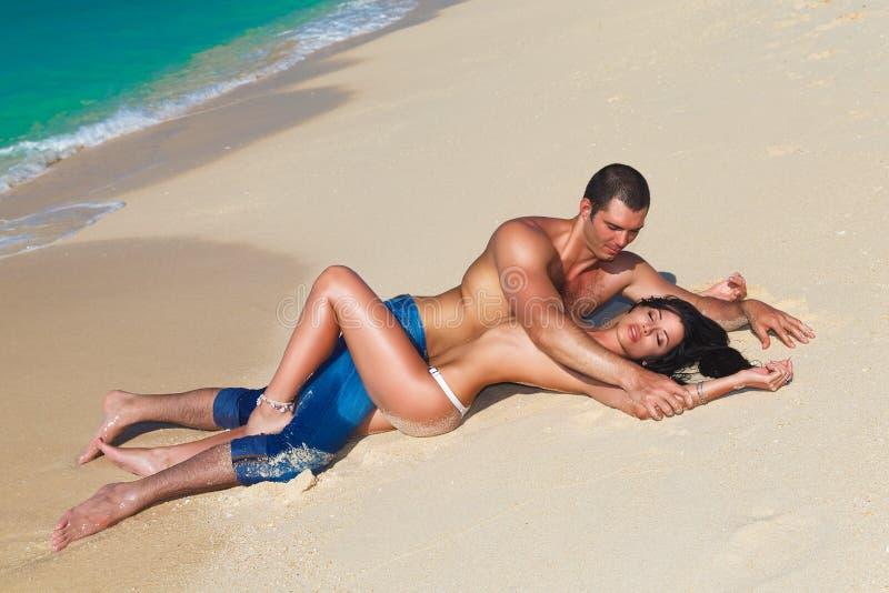Pares que se besan felices de amor jovenes en la playa tropical, poniendo en s imagen de archivo libre de regalías