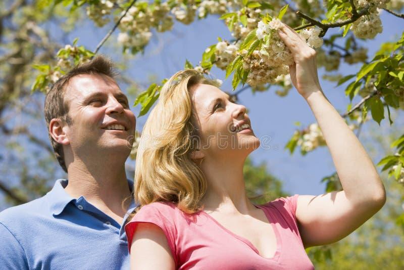 Pares que se colocan al aire libre que celebran la sonrisa del flor imágenes de archivo libres de regalías