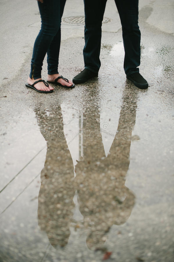 Pares que se colocan en la reflexión de la calle en agua. imagen de archivo libre de regalías