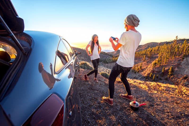 Pares que se divierten cerca del coche fotografía de archivo libre de regalías
