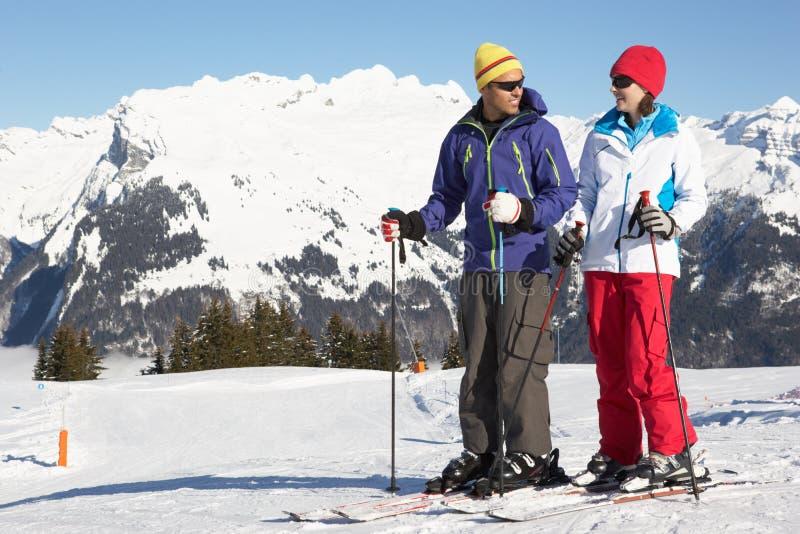 Pares que se divierten el día de fiesta del esquí en montañas imagenes de archivo