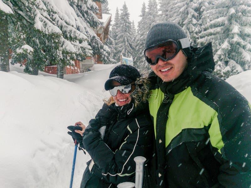 Pares que se divierten el día de fiesta del esquí en montañas fotos de archivo libres de regalías