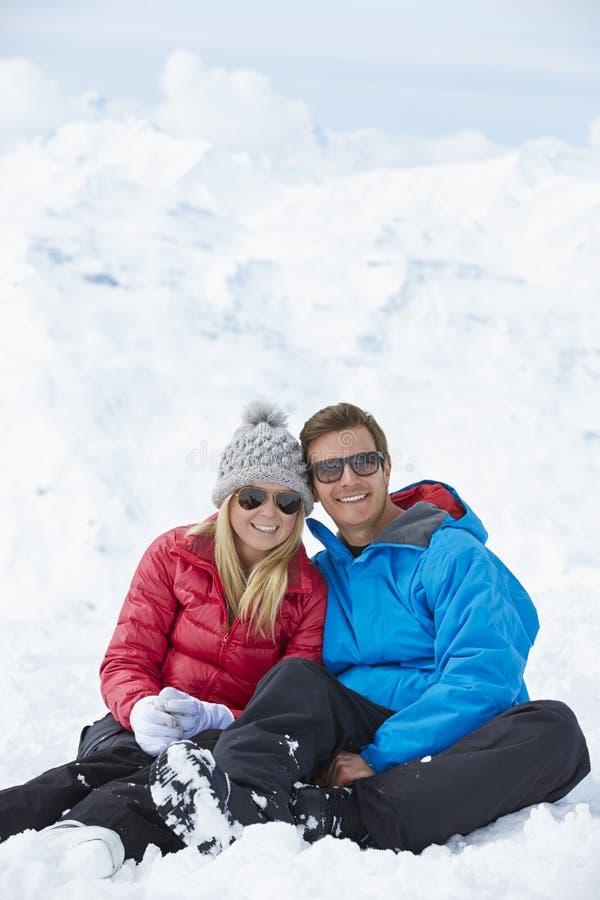 Pares que se divierten el día de fiesta del esquí en montañas foto de archivo
