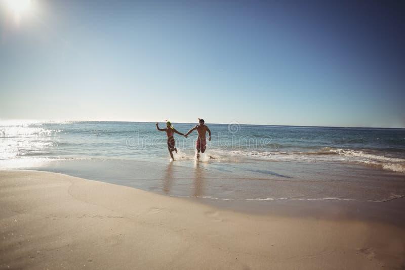 Pares que se ejecutan en la playa imágenes de archivo libres de regalías