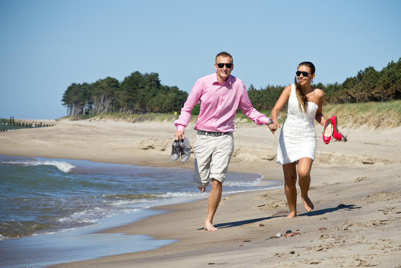 Pares que se ejecutan en la playa por el mar imágenes de archivo libres de regalías