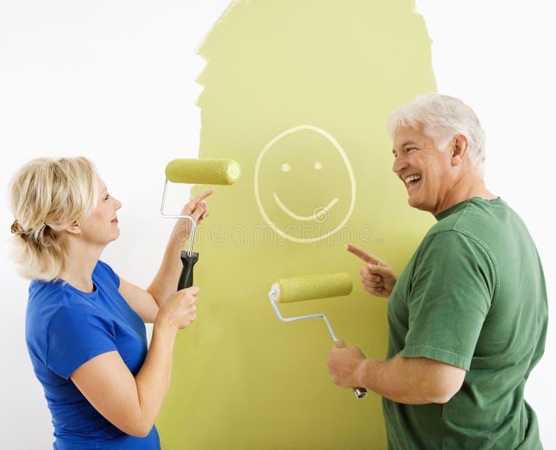 Pares que se ríen de la pintura sonriente de la cara. fotos de archivo