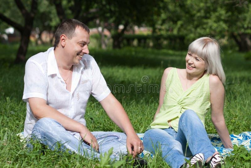 Pares que se reclinan sobre la hierba imagenes de archivo