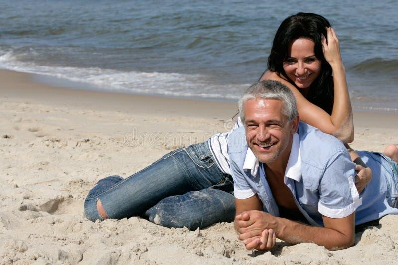 Pares que se reclinan sobre la playa imagen de archivo libre de regalías