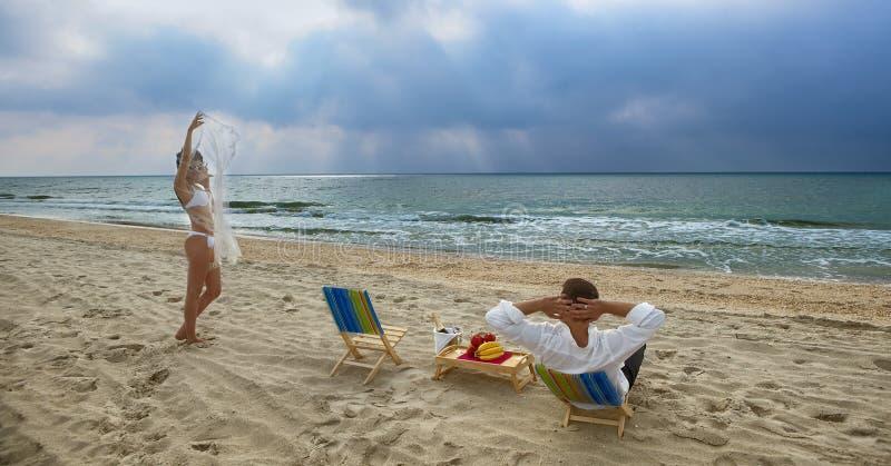 Pares que se reclinan sobre la playa fotos de archivo libres de regalías