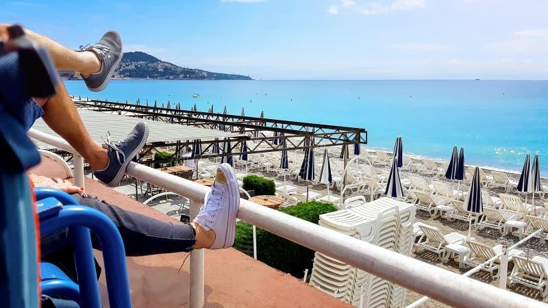 Pares que se relajan cerca Niza de la playa vacía, turismo en Francia, tranquilidad de los turistas imagen de archivo libre de regalías