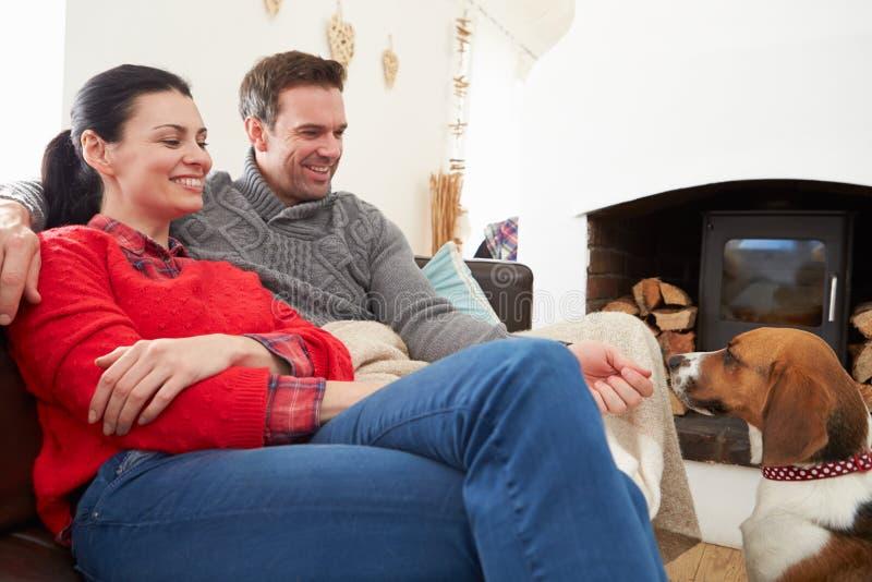 Pares que se relajan en casa con el perro casero fotos de archivo libres de regalías