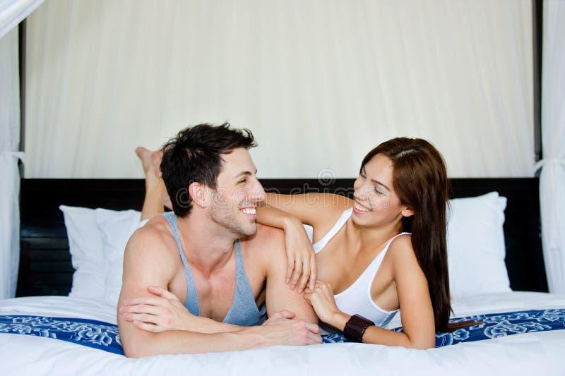 Pares que se relajan en dormitorio imagen de archivo libre de regalías