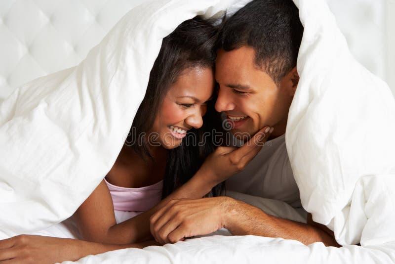 Pares que se relajan en la cama que oculta debajo del edredón fotos de archivo libres de regalías