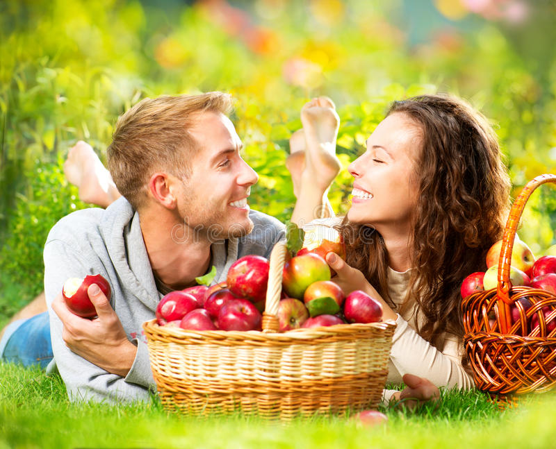 Pares que se relajan en la hierba y que comen manzanas imagen de archivo libre de regalías