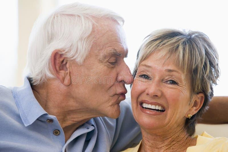 Pares que se relajan en la sala de estar que se besa y que sonríe imagen de archivo libre de regalías