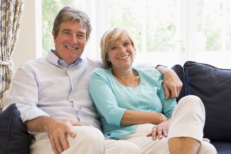 Pares que se relajan en la sonrisa de la sala de estar imagen de archivo