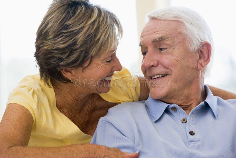 Pares que se relajan en la sonrisa de la sala de estar fotos de archivo