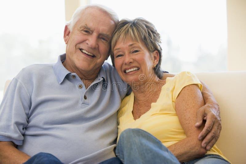 Pares que se relajan en la sonrisa de la sala de estar imagen de archivo libre de regalías