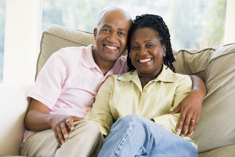 Pares que se relajan en sala de estar y la sonrisa imagenes de archivo