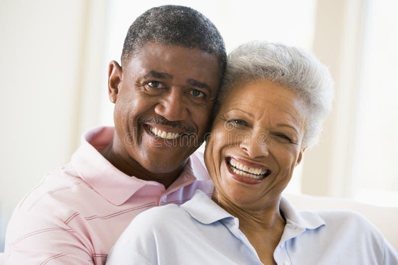 Pares que se relajan en sala de estar y la sonrisa imagen de archivo libre de regalías