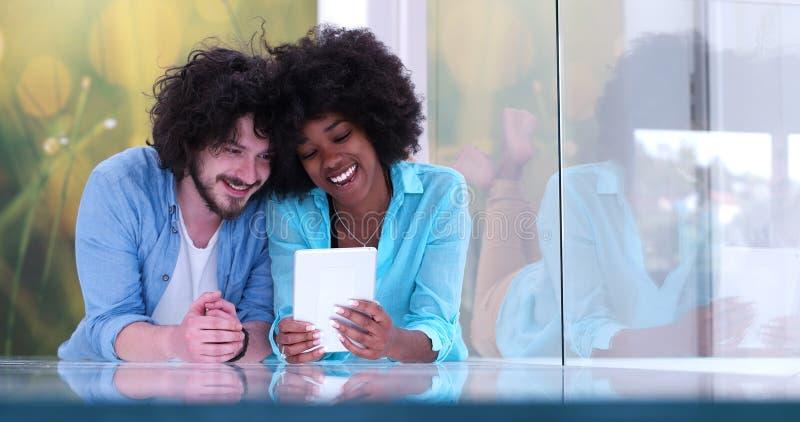 Pares que se relajan junto en casa con la tableta imagen de archivo