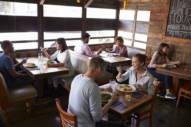 Pares que se relajan sobre el almuerzo en un restaurante, visión elevada imagenes de archivo
