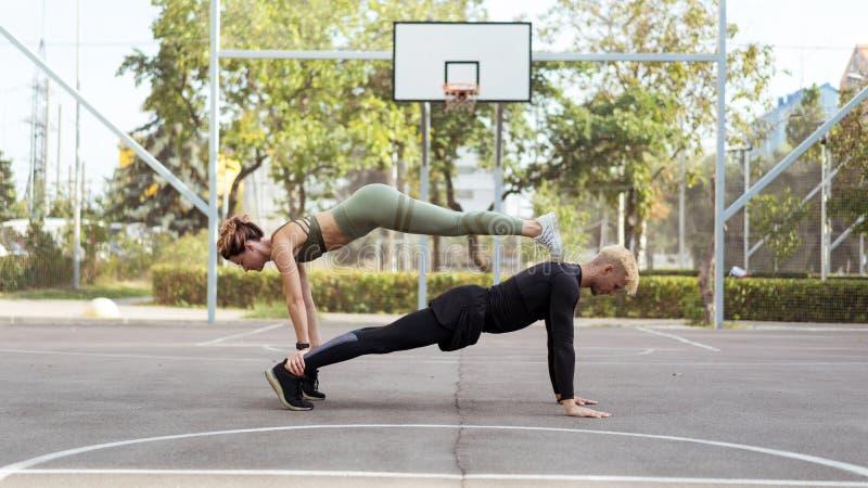 Pares que se resuelven en un sportsground, haciendo un ejercicio del tablón del recto-brazo foto de archivo