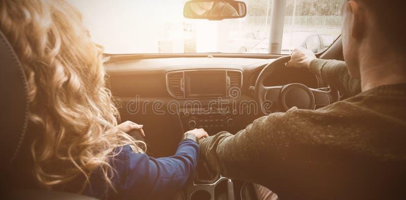 Pares que se sientan en coche durante la prueba de conducción imagen de archivo libre de regalías