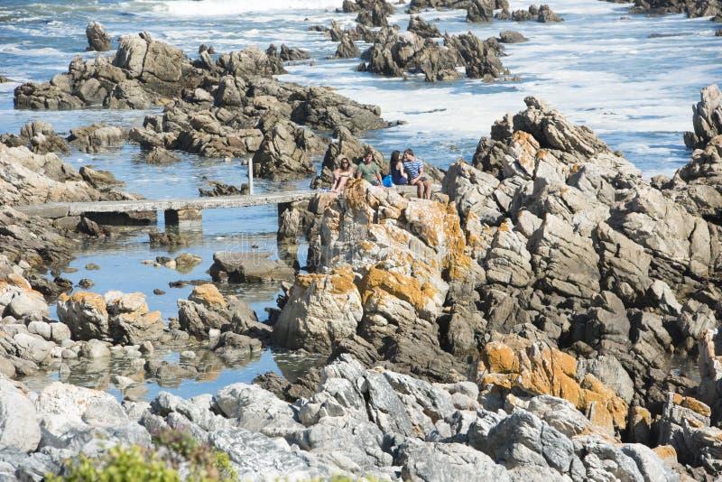 Pares que se sientan en costa sur rocosa de las orillas, S A fotos de archivo libres de regalías