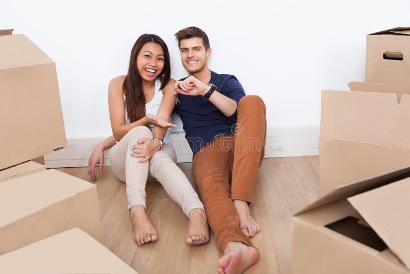 Pares que se sientan en el piso que lleva a cabo llaves de su nuevo hogar imagen de archivo libre de regalías