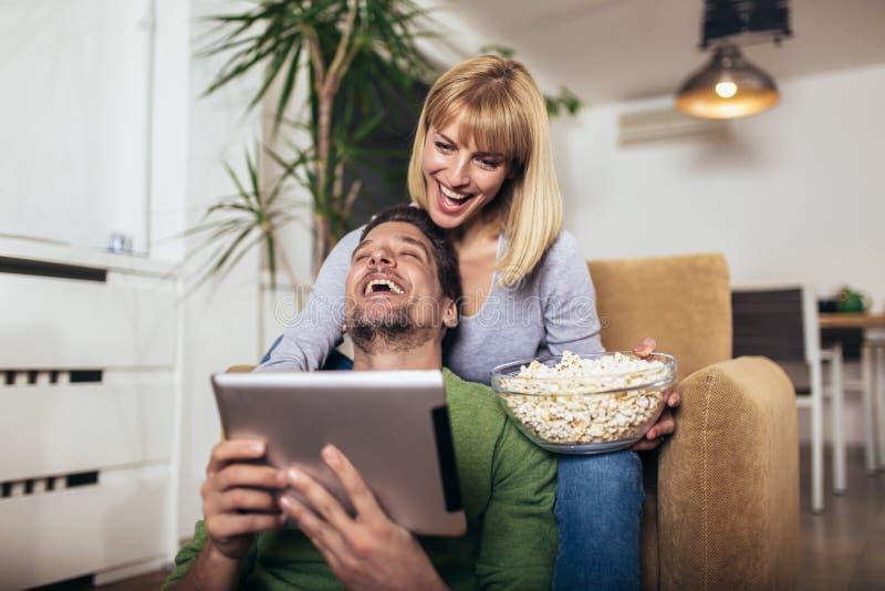 Pares que se sientan en el sofá en una sala de estar y que miran la tableta digital imágenes de archivo libres de regalías