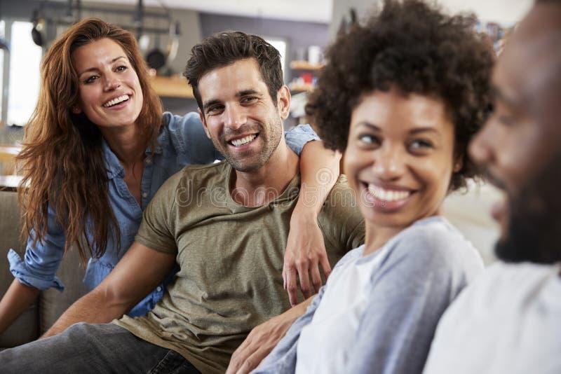 Pares que se sientan en hablar de Sofa With Friends At Home imágenes de archivo libres de regalías