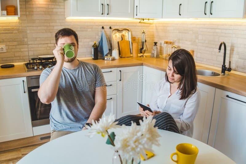 Pares que se sientan en la cocina en las noticias de consumición de la lectura del té de la mañana imágenes de archivo libres de regalías