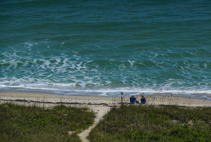 Pares que se sientan en la playa que mira el océano imagen de archivo