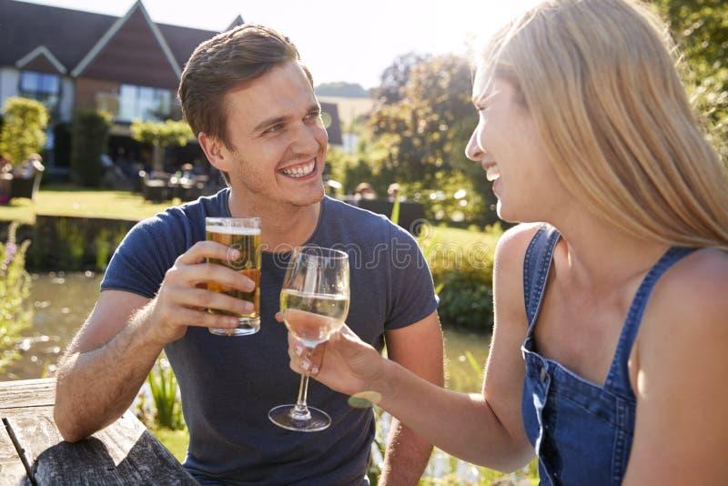 Pares que se sientan en la tabla que disfruta de la bebida al aire libre del verano en el Pub fotografía de archivo