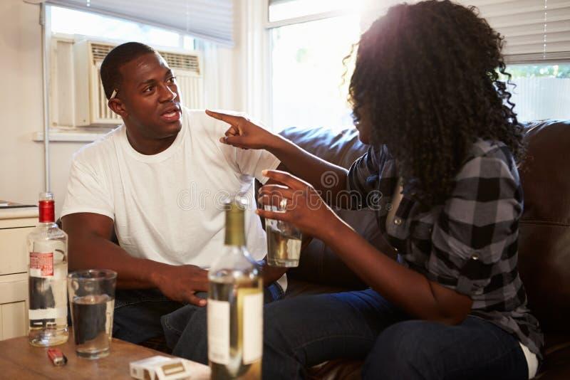 Pares que se sientan en Sofa Drinking Alcohol And Arguing foto de archivo