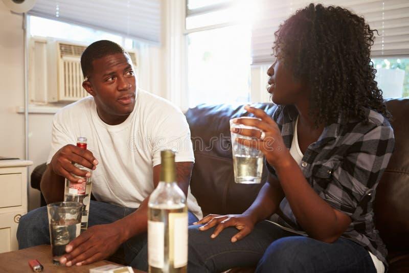 Pares que se sientan en Sofa Drinking Alcohol And Arguing imagenes de archivo
