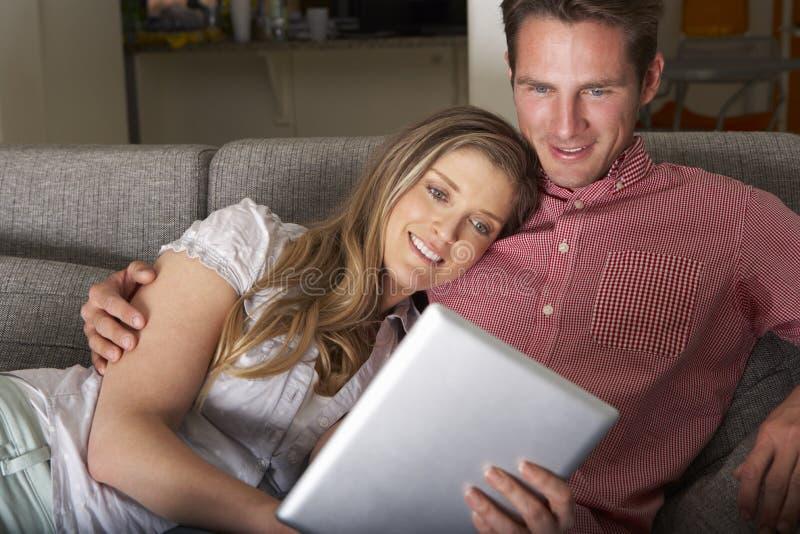 Pares que se sientan en Sofa Looking At Digital Tablet imágenes de archivo libres de regalías
