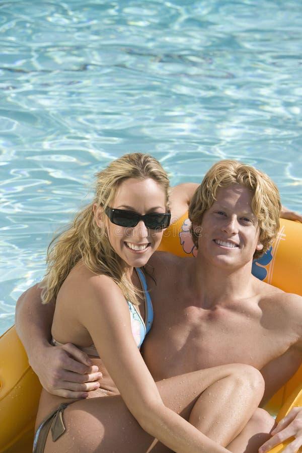 Pares que se sientan en una balsa inflable en piscina imagenes de archivo