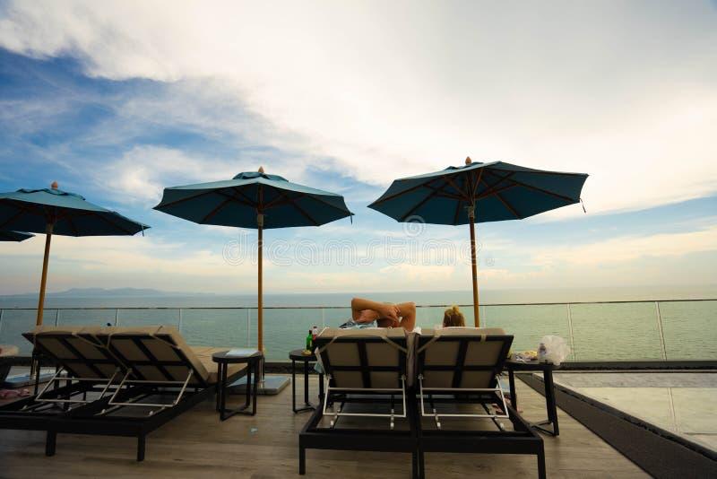 Pares que se sientan junto por la piscina Conceptos de las vacaciones y de la relajaci?n imagenes de archivo