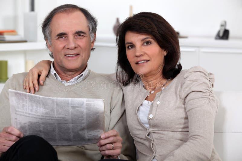 Pares que se sientan leyendo un periódico foto de archivo libre de regalías