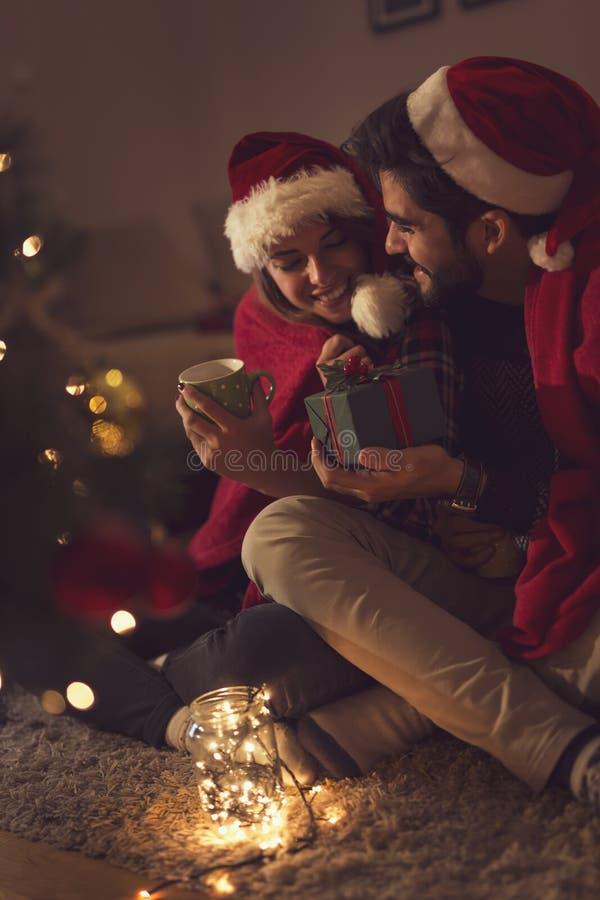 Pares que sentam-se ao lado da árvore de Natal imagens de stock