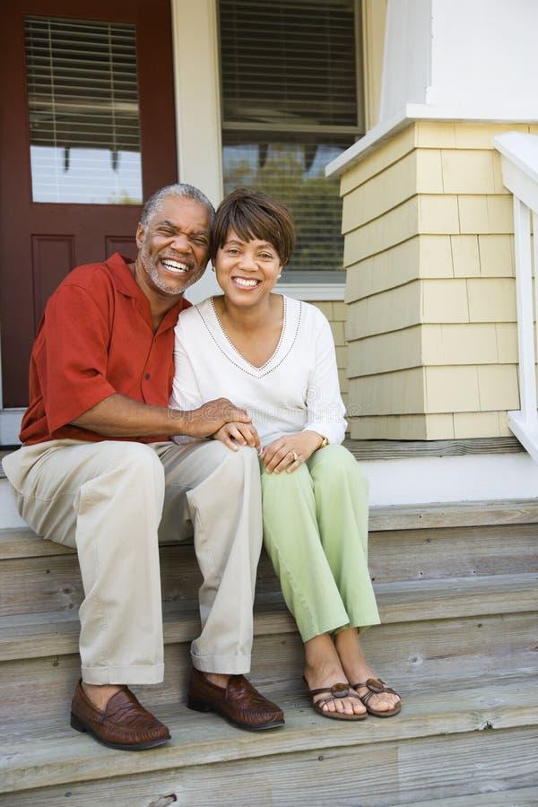 Pares que sentam-se em etapas ao ar livre do sorriso Home foto de stock royalty free