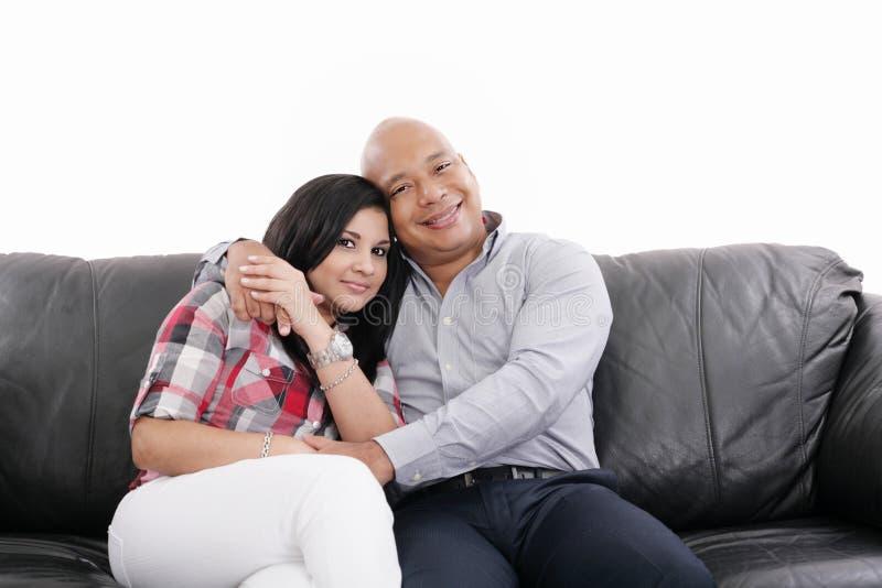 Pares que sentam-se em um sofá fotografia de stock royalty free