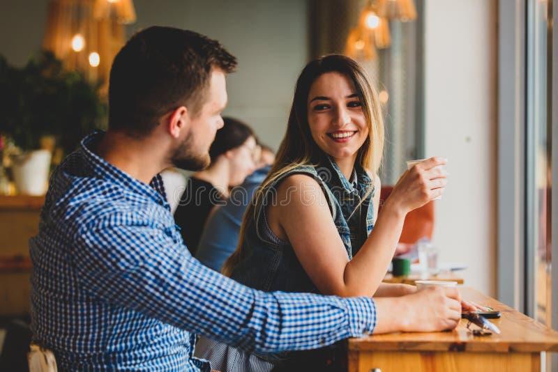 Pares que sentam-se em uma tabela em um café e em um café bebendo foto de stock